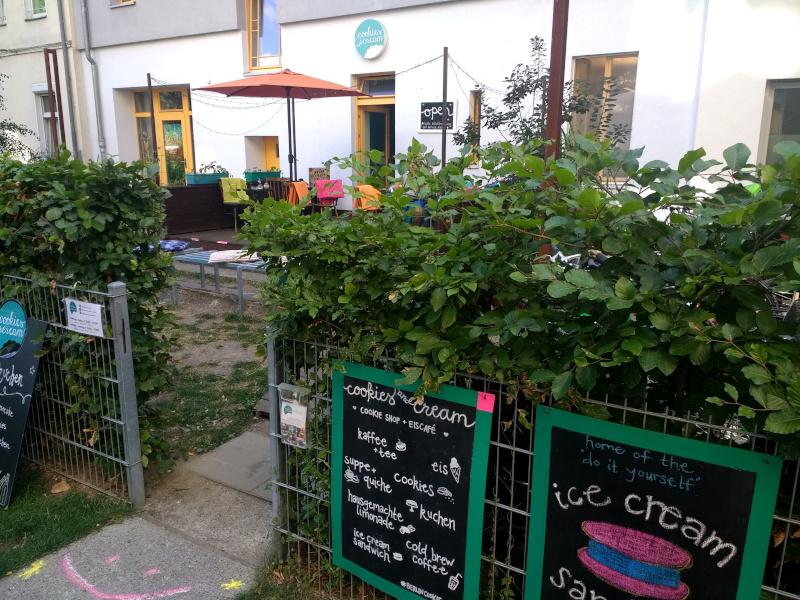 Gartenhecke und bunte Schilder vor Cafégarten
