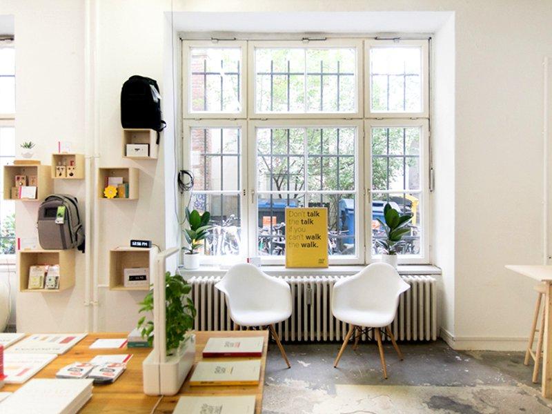 Blick in einen hellen Raum mit Betonboden, einige Produkte liegen auf einem Holztisch