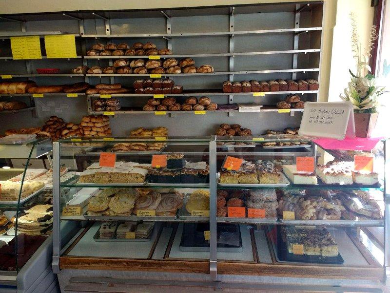 Auslage einer Bäckerei mit Kuchen, Brot und Brötchen