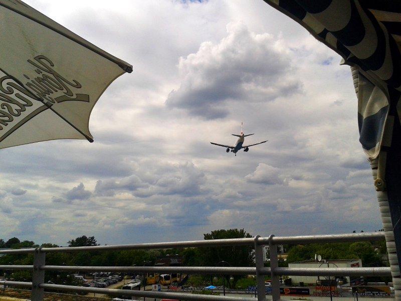 Flugzeug überfliegt Biergarten auf dem Weg zur Landebahn