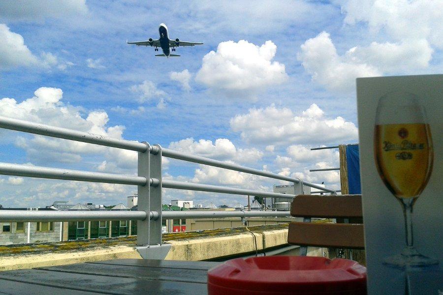 flugzeug überfliegt einen biergarten