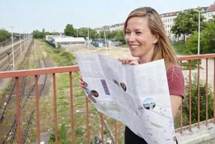 Junge Frau mit Stadtplan auf Brücke in Berlin