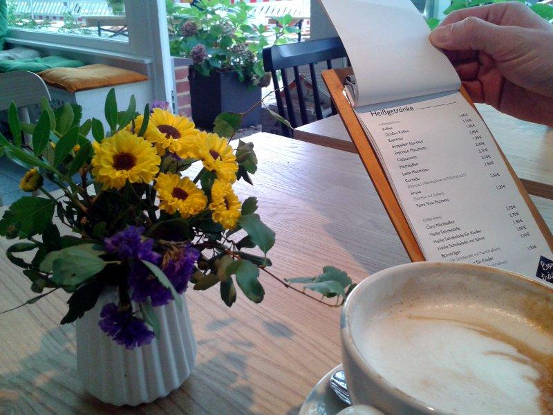 Kaffee, Blumen und Speisekarte im Vordergrund, im Hintergund eine weiße Holzbank