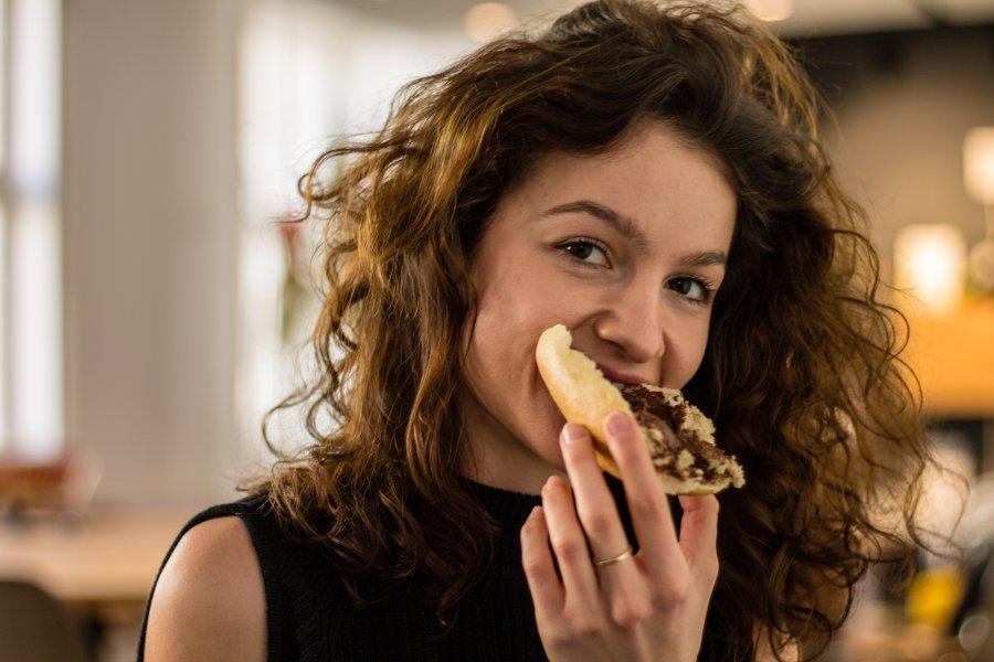 Julia beißt in ein Brötchen mit ihrem Kaffe-Schoko-Aufstrich