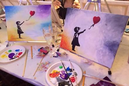 Zwei selbst gemalte Bilder mit einem Banksy-Motiv auf einem Tisch mit Farben