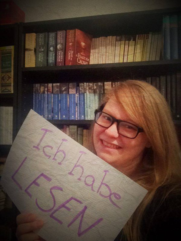 Frau vor Buchregal mit dem Schild: Ich habe Lesen