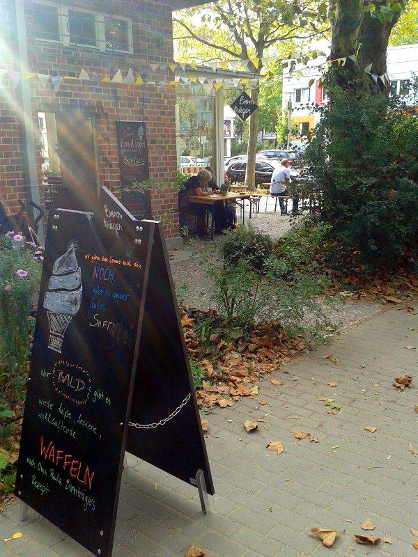 Bunte Speisetafel vor altem Backsteinbau-Café