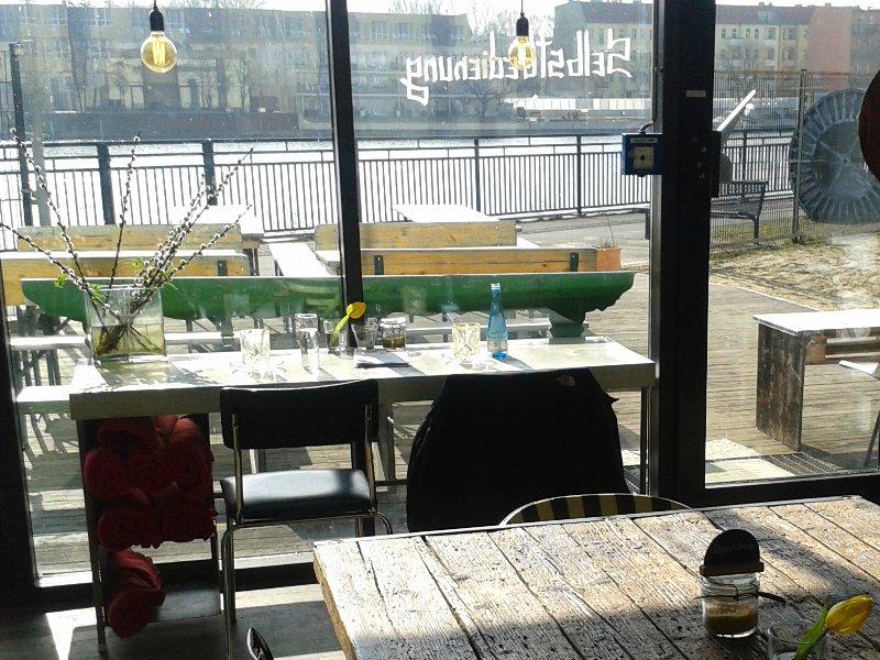 Holztisch im Vordergrund, im Hintergrund ein großes Fenster mit Blick auf Terrasse und Spree