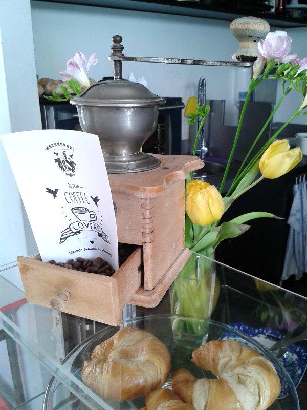 Alte Kaffeehandmühle auf einem Tresen mit Croissants