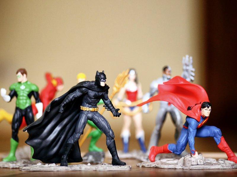Spielfiguren von Actionhelden stehen auf einer glatten Fläche