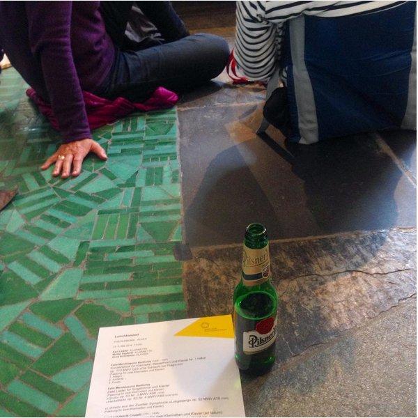 Zwei Leute sitzen auf dem Boden, hinter ihnen steht eine Bierflasche