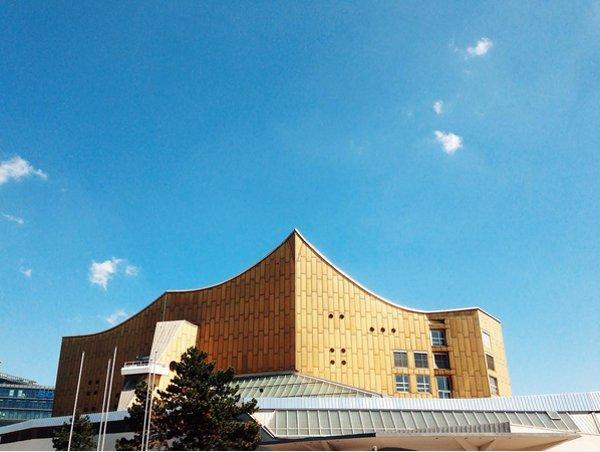 Ein hellbraunes Gebäude mit Spitzdach vor blauem Himmel