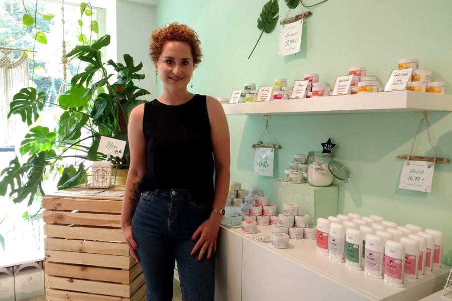 Frau steht vor Regalen mit Kosmetikprodukten