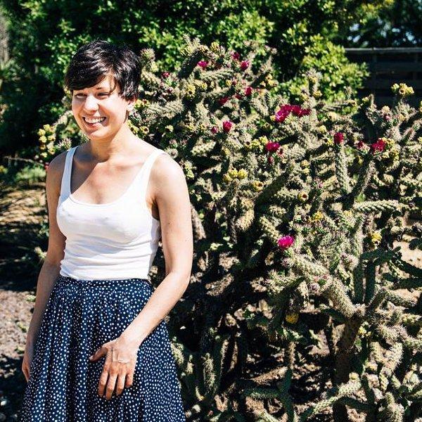 Junge Frau vor blühendem Strauch im Sommer