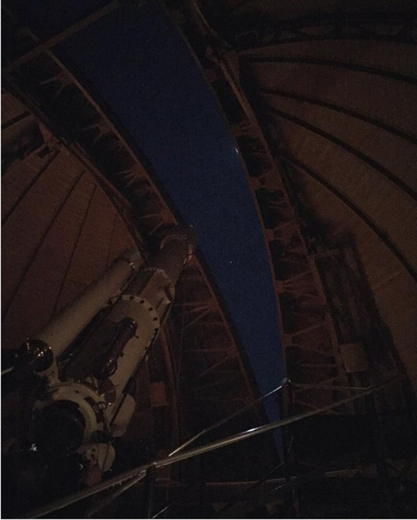 Ein Fernrohr blickt durch eine Öffnung in einer Kuppel in den Weltraum