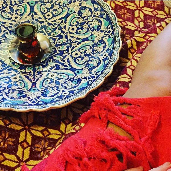Frauenbein in Decke neben einem Glas türkischen Tees