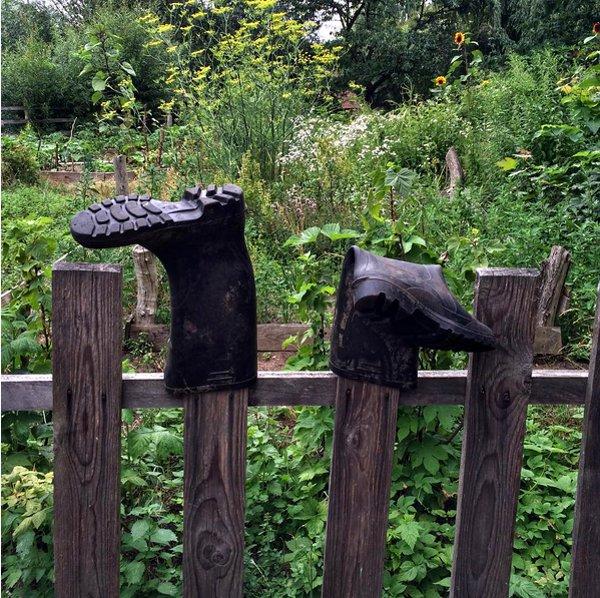 Gummistiefel stecken auf einem Holzzaun