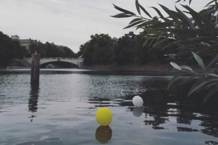 Ein gelber Luftballon treibt auf dem Wasser