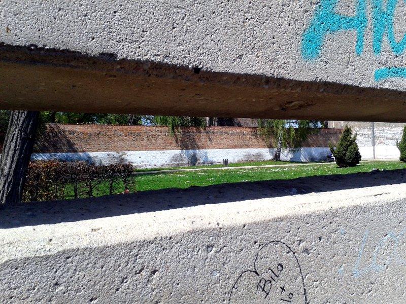Blick durch einen Spalt in Betonwänden auf einen Park