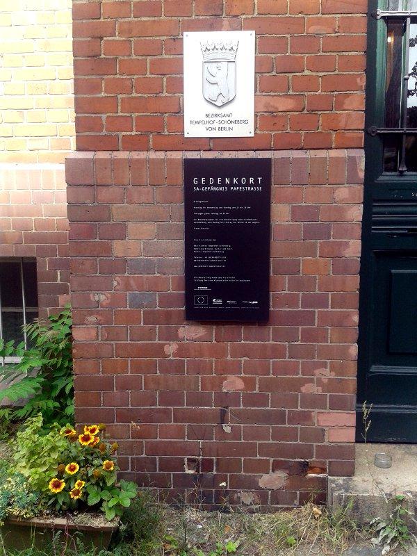 Hinweistafel neben Haustür an Backsteingebäude