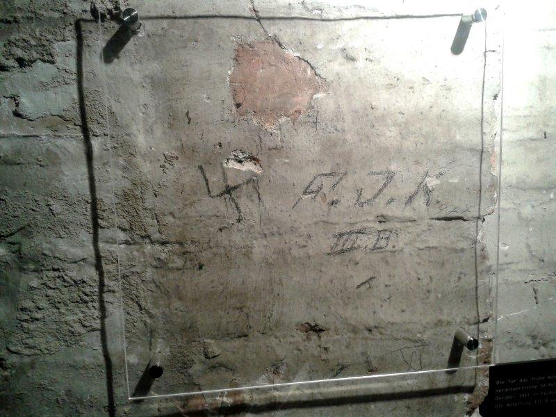 An einer Kellerwand steht mit Bleistift ein Hakenkreuz und FJK 3b