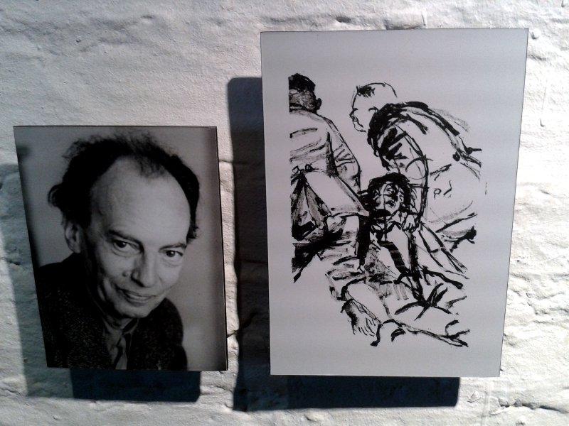 Das Foto eines Mannes hängt neben einer Zeichnung, auf der zwei Uniformierte einen halb Bewusstlosen hinter sich herzerren