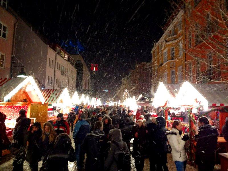 Menschen zwischen Weihnachtsmarktbuden im Schneegestöber