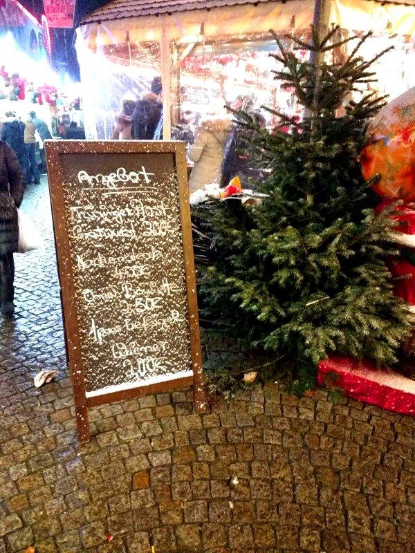 Puderschnee auf Angebotsschild, daneben ein Tannenbaum